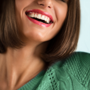 woman in green sweater smiling with dental crowns